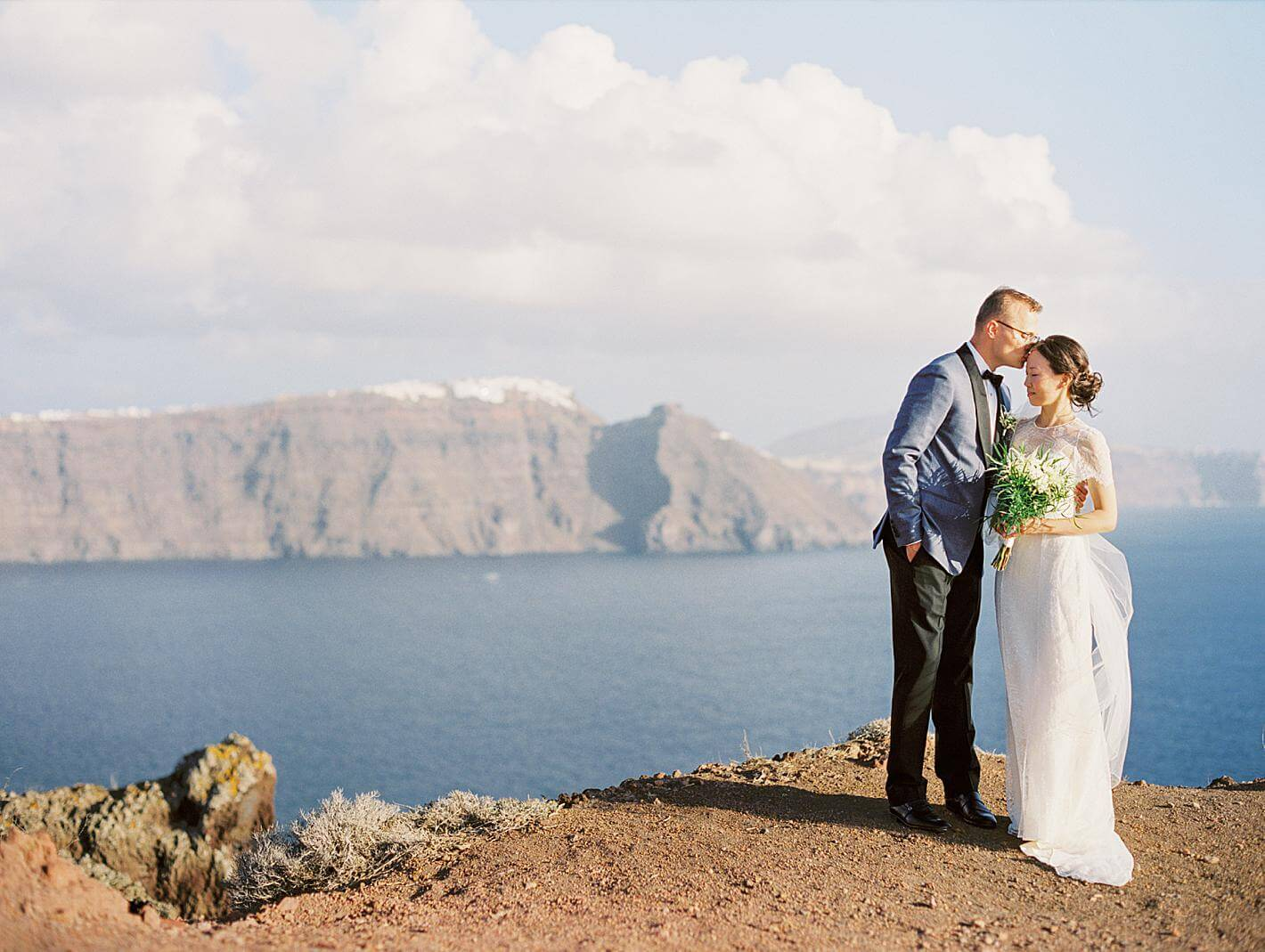 bride and groom portrait at a santorini wedding at a cliff at santorini