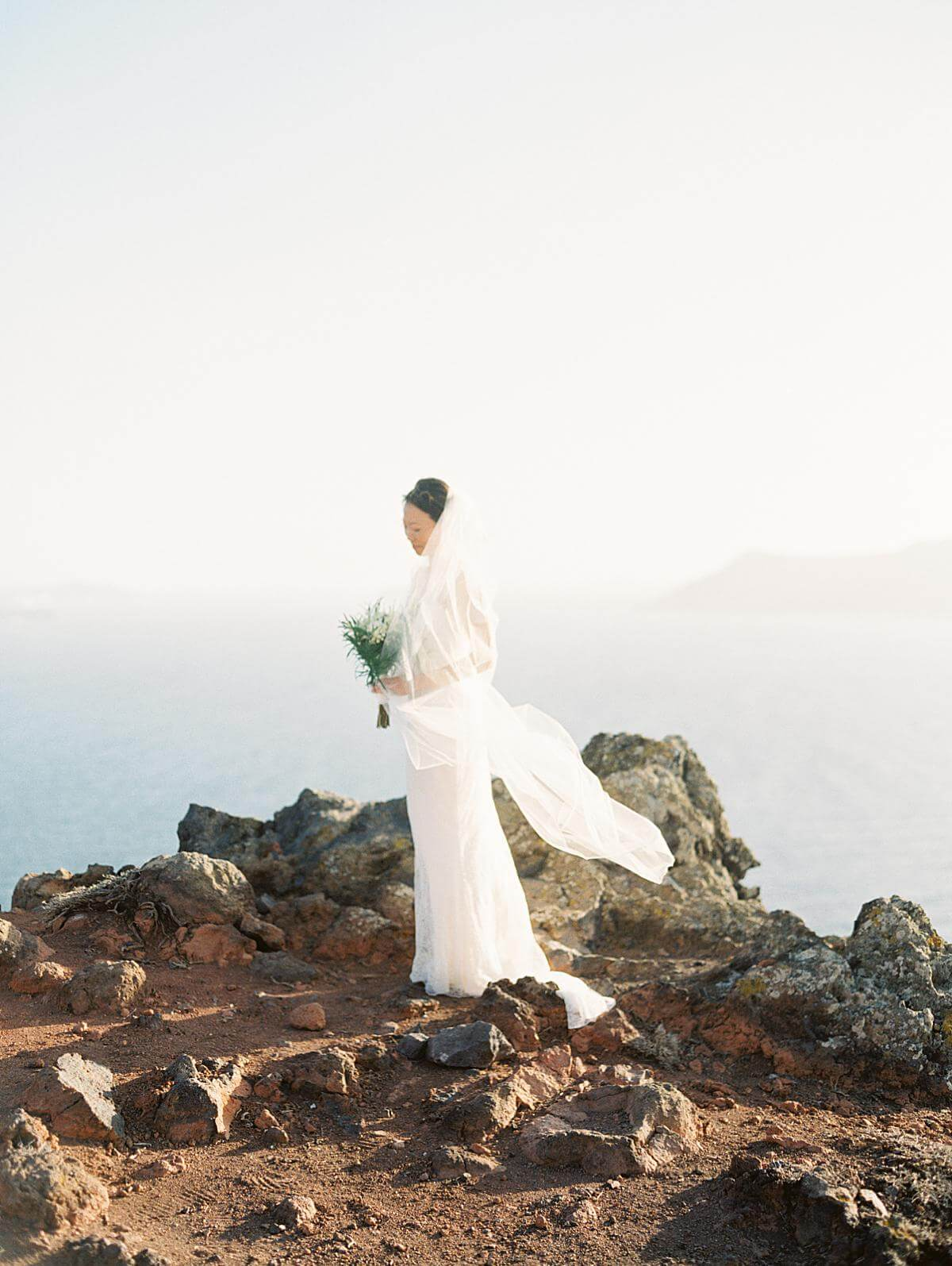 bride in white dress with long veil portrait at a santorini wedding at a cliff at santorini