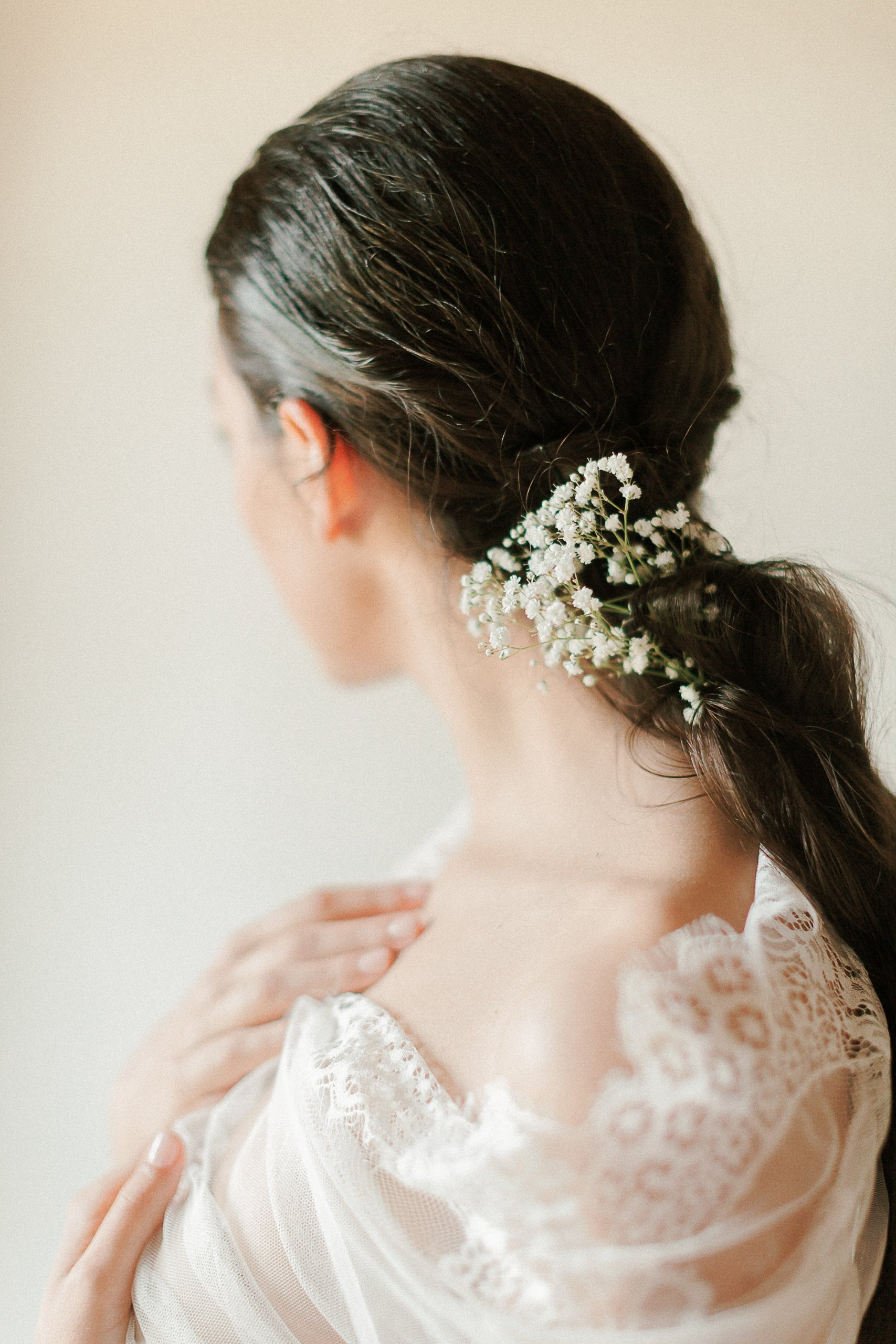 Close up of model wearing little white flowers on her hair for a bridal boudoir session